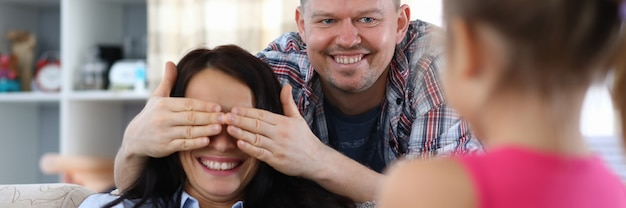 Portrait de père souriant, fermant les yeux de la mère.
