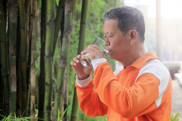 Portrait d'une personne âgée buvant de l'eau à l'aide d'un verre