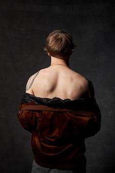 Portrait d'une personne hipster avec corps tatoué en veste pose sur fond sombre