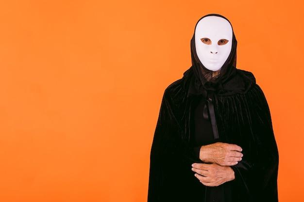 Portrait d'une personne en masque d'halloween tueur blanc, cape et capuche regardant la caméra, habillée pour halloween sur fond orange, avec espace de copie à gauche