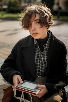 Portrait de personne non binaire tenant une tablette