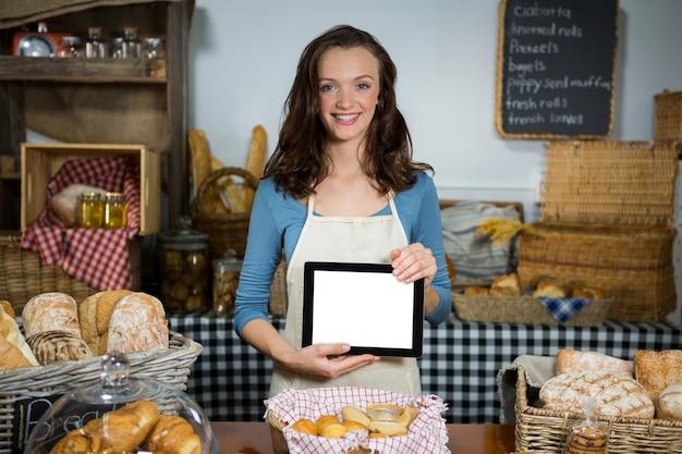 Portrait de personnel souriant montrant tablette numérique au comptoir de la boulangerie