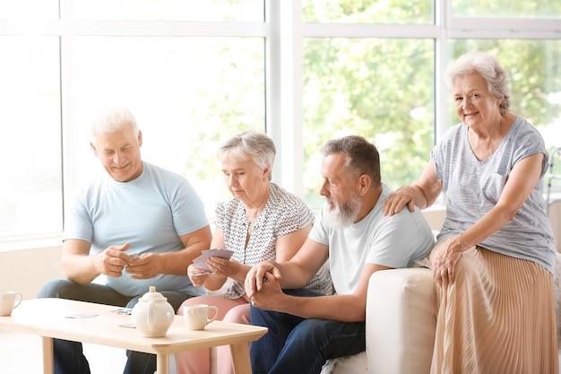 Portrait de personnes âgées jouant aux cartes en maison de retraite