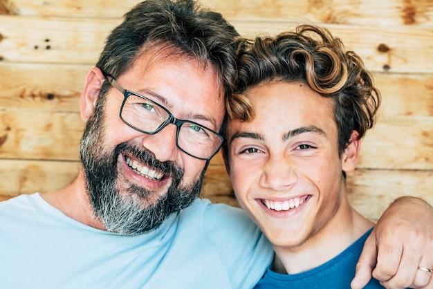 Portrait de personnes gaies avec père et fils s'embrassent et rient beaucoup ensemble s'amusant et regardant la caméra