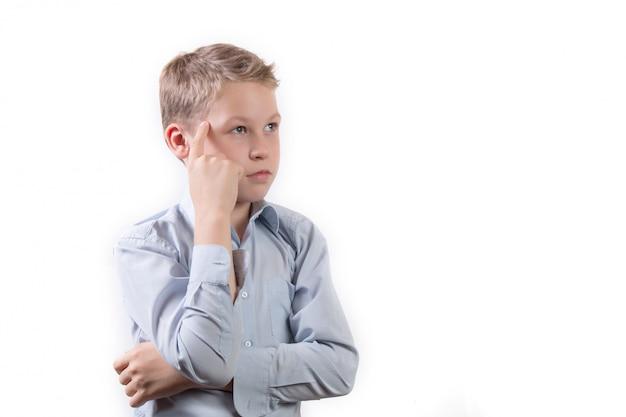 Portrait d'un petit écolier dans une pose pensive isolé sur fond blanc
