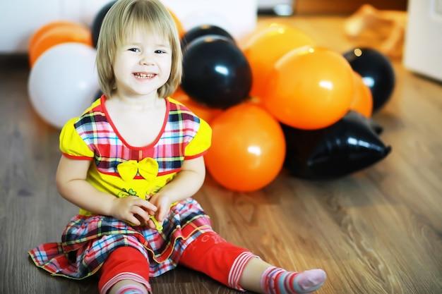 Portrait d'un petit enfant allongé sur le sol dans une pièce décorée de ballons. concept d'enfance heureuse.