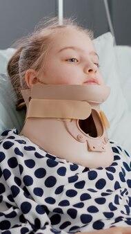 Portrait d'un petit enfant hospitalisé portant un collier cervical après avoir subi un accident traumatique