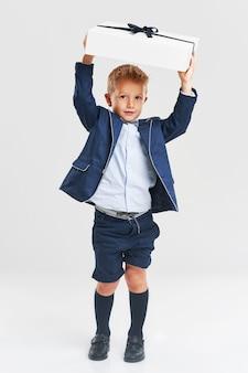Portrait d'un petit enfant mignon et heureux tenant une boîte-cadeau et regardant la caméra isolée sur fond gris