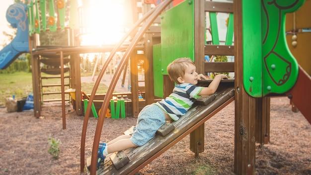Portrait d'un petit garçon actif rampant et grimpant sur un escalier en bois sur une aire de jeux pour enfants au parc