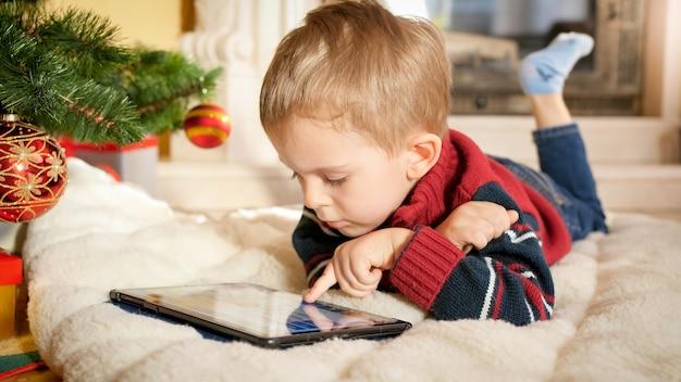 Portrait de petit garçon allongé sur une couverture à côté de l'arbre de noël et jouant sur une tablette numérique