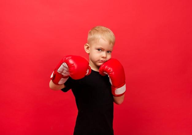 Portrait d'un petit garçon athlète dans des gants de boxe rouges faisant un coup de poing sur le rouge