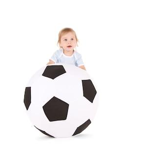 Portrait de petit garçon avec ballon de football sur mur blanc