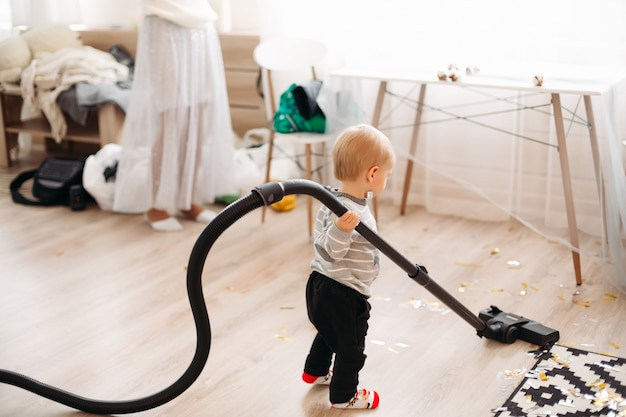 Portrait de petit garçon blond en pull gris et jean noir nettoyage des confettis
