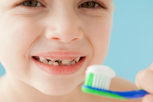 Portrait de petit garçon avec brosse à dents sur fond bleu