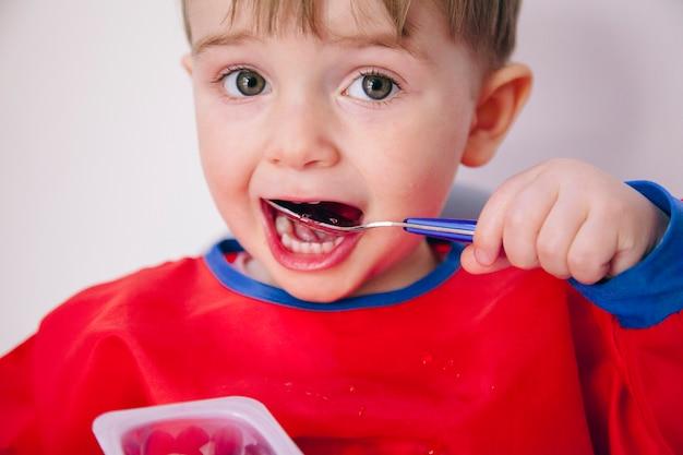 Portrait d'un petit garçon curieux apprenant à manger. mode de vie familial et sain.