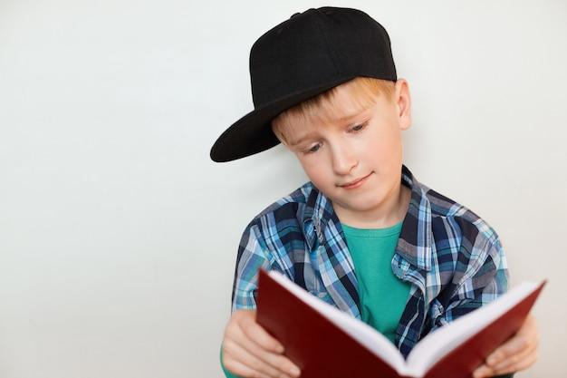 Un portrait de petit garçon curieux en casquette noire et chemise colorée à carreaux lire l'encyclopédie à la recherche dans le livre avec intérêt