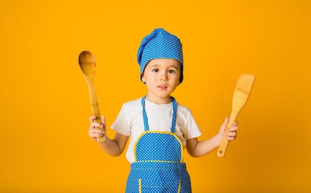 Portrait d'un petit garçon dans un chapeau de chef et un tablier avec des cuillères en bois sur une surface jaune avec un espace pour le texte