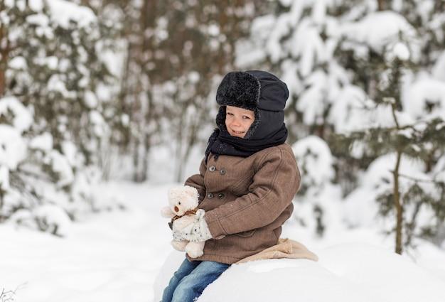 Portrait d'un petit garçon dans une forêt d'hiver