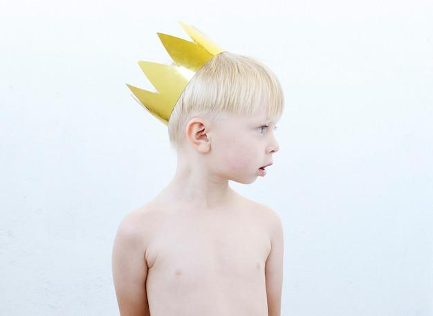 Portrait d'un petit garçon drôle une couronne d'or sur sa tête