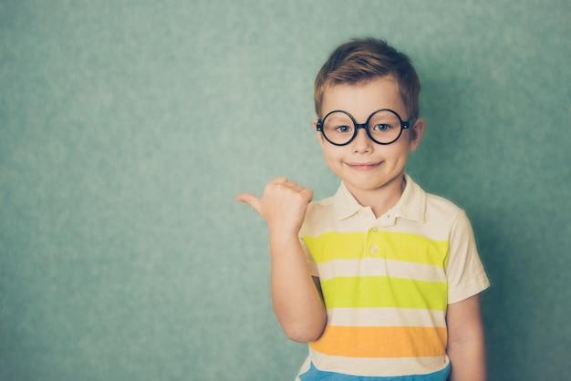 Portrait de petit garçon élégant avec le doigt du doigt aux points sur le côté.