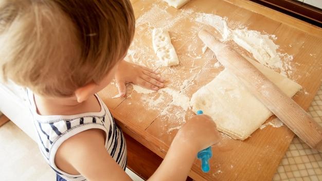 Portrait de petit garçon faisant de la pâte sur un comptoir de cuisine en bois