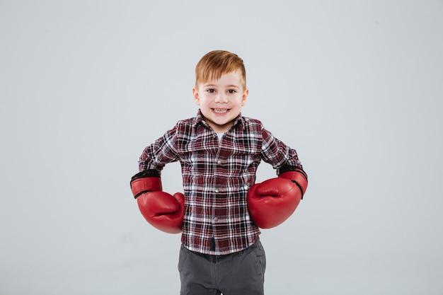 Portrait de petit garçon heureux en chemise à carreaux et gants de boxe rouges sur mur blanc