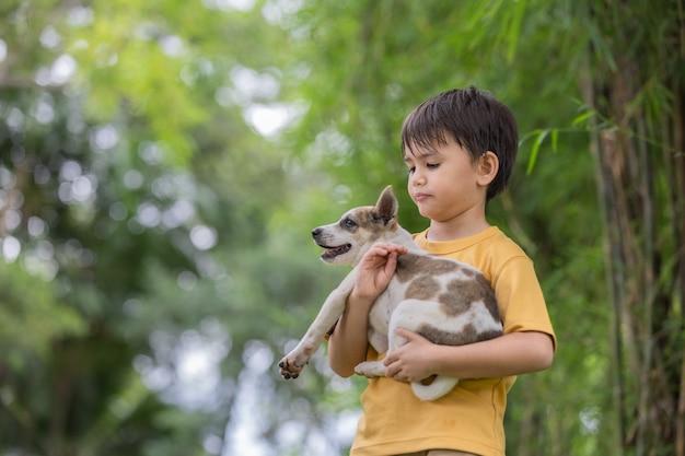 Portrait d'un petit garçon heureux jouant avec son adorable chiot