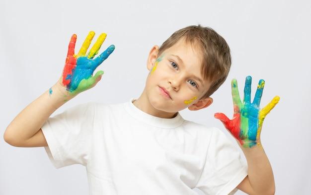 Portrait d'un petit garçon heureux avec des peintures sur les mains isolées sur fond blanc
