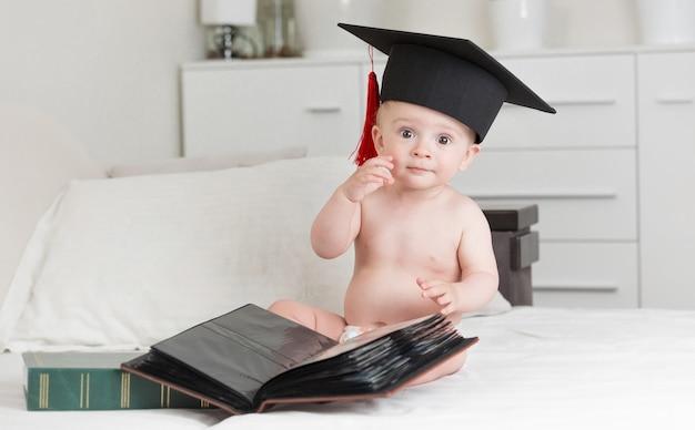 Portrait d'un petit garçon intelligent en chapeau de graduation posant avec des livres