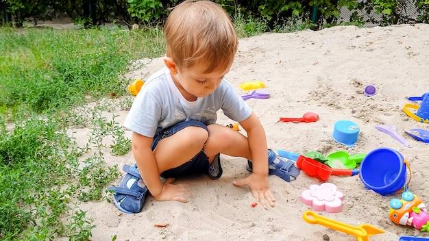 Portrait de petit garçon jouant avec des jouets et du sable sur l'aire de jeux