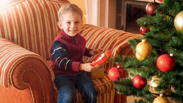 Portrait d'un petit garçon joyeux et joyeux assis dans un fauteuil et ouvre sa boîte de cadeau de noël du père noël
