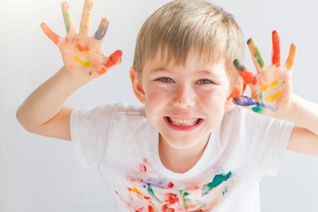 Portrait de petit garçon joyeux avec les mains peintes colorées