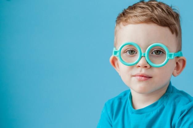 Portrait d'un petit garçon à lunettes jouet sur fond bleu