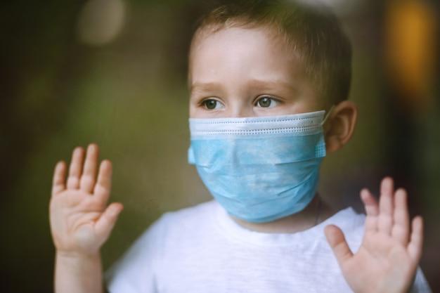 Portrait de petit garçon avec masque médical regardant la caméra dans la ville