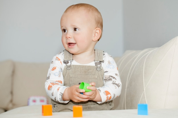 Portrait de petit garçon mignon caucasien jouant des blocs colorés de différentes formes. apprendre en jouant le concept d'école à domicile de formation cérébrale.