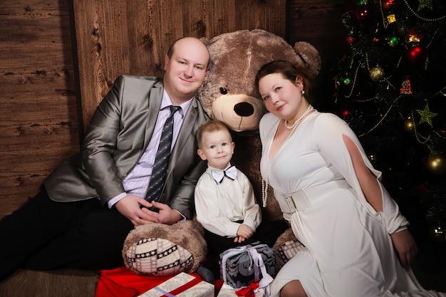Portrait de petit garçon et parents heureux tenant le cadeau de noël