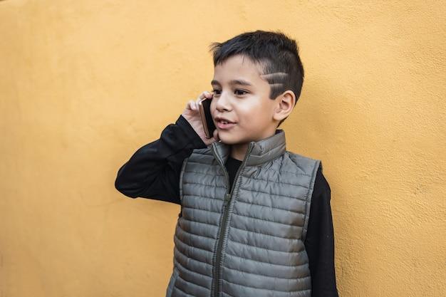 Portrait d'un petit garçon parlant sur un smartphone.