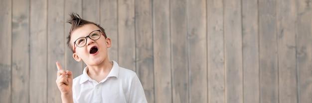 Portrait de petit garçon portant des lunettes et un t-shirt blanc à la surface en bois