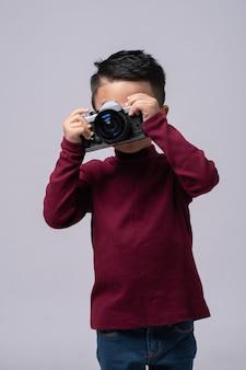 Portrait de petit garçon portant un pull rouge debout isolé sur fond gris