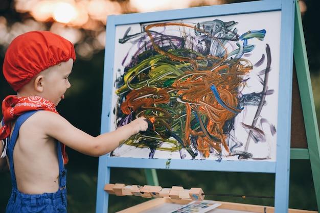 Portrait d'un petit garçon qui sourit d'embarras et se réjouit de la peinture dans ses mains