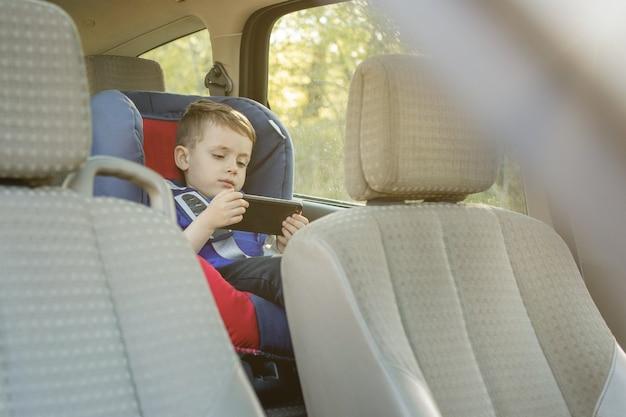 Portrait d'un petit garçon s'ennuie assis dans un siège d'auto. sécurité du transport des enfants.
