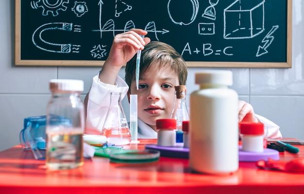 Portrait de petit garçon scientifique extrayant le liquide du tube à essai derrière la table avec des jouets chimiques