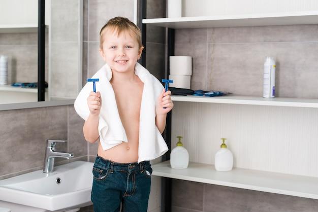 Portrait, petit, garçon, serviette, tour cou, tenue, rasoir bleu, mains, debout, salle bains