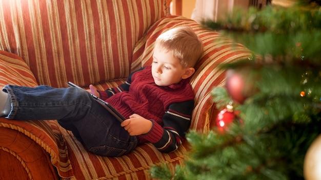 Portrait d'un petit garçon souriant allongé sur un canapé à côté d'un bel arbre de noël dans le salon et jouant sur une tablette numérique