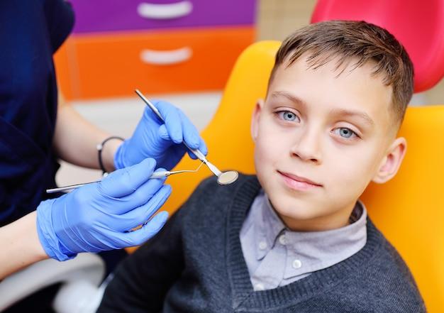 Portrait d'un petit garçon souriant dans un fauteuil dentaire.