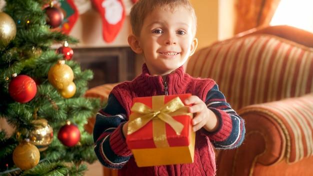 Portrait de petit garçon souriant donnant une boîte avec un cadeau de noël à huis clos. image parfaite pour les vacances d'hiver et les fêtes