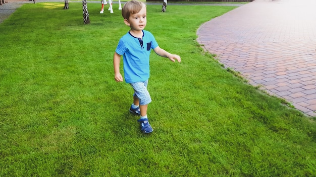 Portrait de petit garçon souriant qui court sur la pelouse du parc