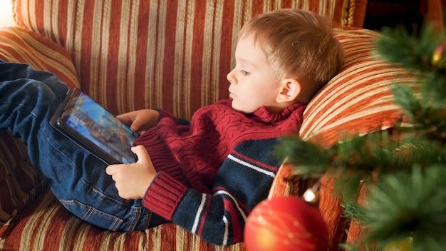 Portrait de petit garçon avec tablette numérique assis dans un fauteuil à côté de l'arbre de noël