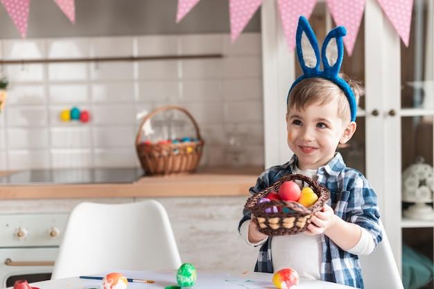 Portrait de petit garçon tenant un panier avec des oeufs de pâques