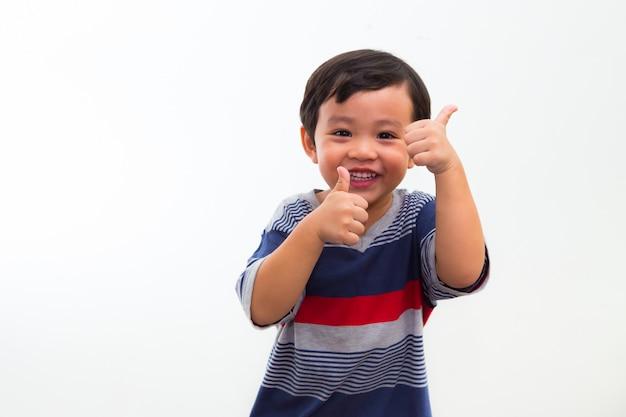 Portrait de petit garçon tient un pouce en studio